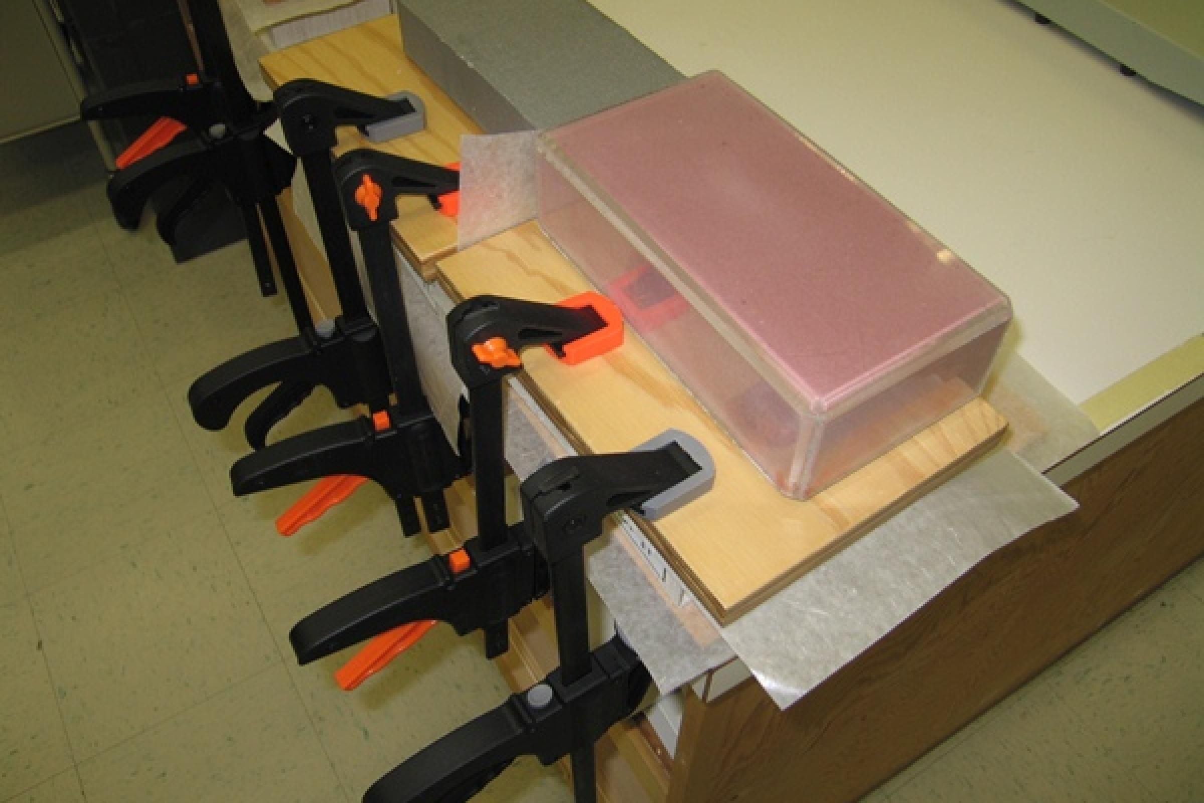 Clamped boxes drying under weights